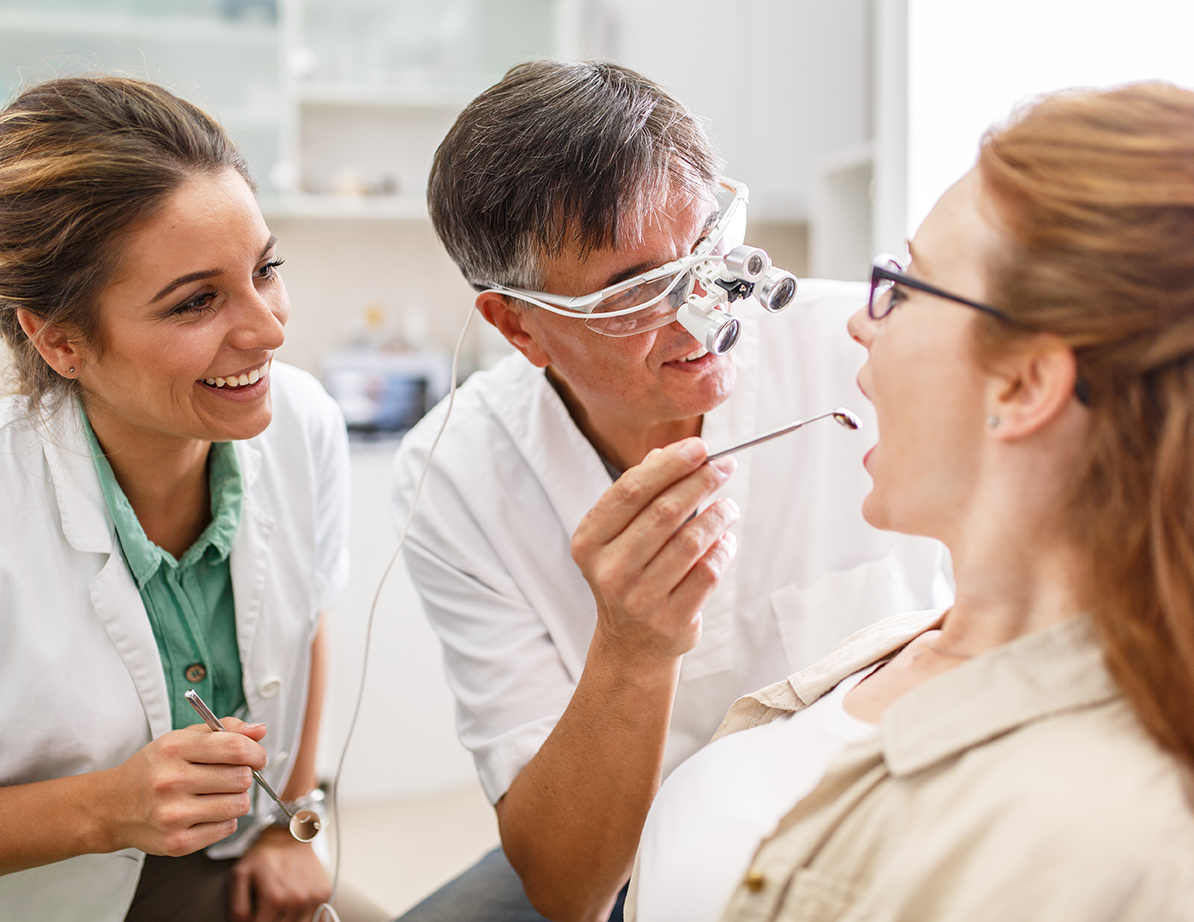 Dentist and hygienst examing patient's mouth